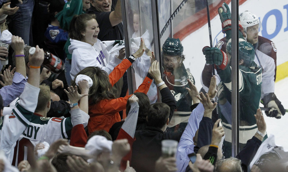 Photo - Minnesota Wild center Mikael Granlund (64), of Finland, pounds on the glass in front of fans after scoring the game-winning goal against Colorado Avalanche goalie Semyon Varlamov during overtime of Game 3 of an NHL hockey first-round playoff series in St. Paul, Minn., Monday, April 21, 2014. The Wild won 1-0 in overtime. (AP Photo/Ann Heisenfelt)