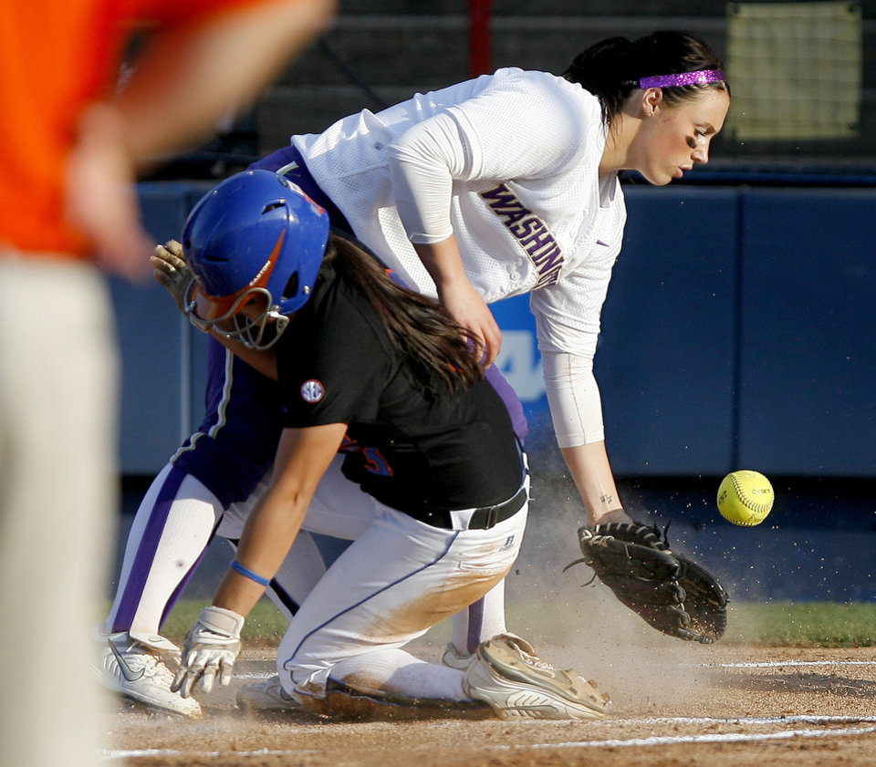 Photo - Aja Paculba, left, of Florida score as Danielle Lawrie tries to catch the ball after a wild pitch in the first inning of the second softball game of the championship series between Washington and Florida in Women's College World Series at ASA Hall of Fame Stadium in Oklahoma City, Tuesday, June 2, 2009. Photo by Bryan Terry, The Oklahoman