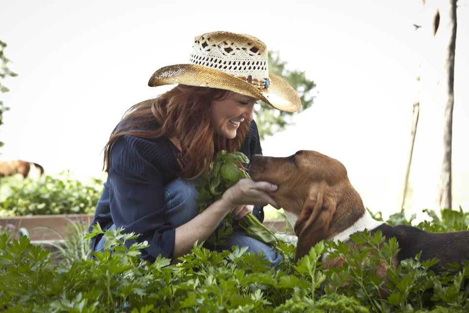 Photo - TV SERIES / TELEVISION SHOW: Ree Drummond - host, picks herbs in her garden during episode 2 as seen on Food Network's The Pioneer Woman Season 1.  *** Ree Drummond with her dog, Charlie. For her new Food Network show,