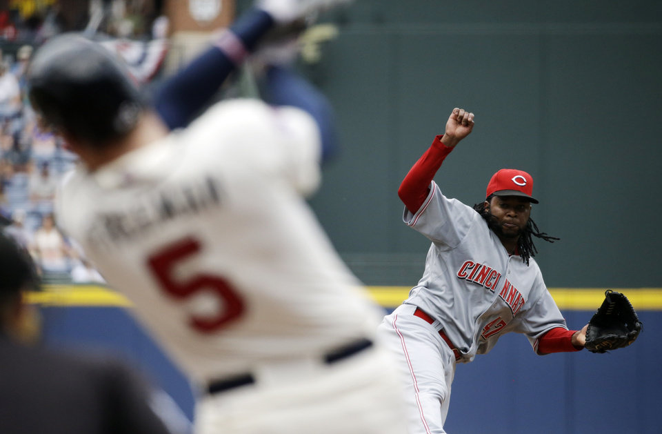 Photo - Cincinnati Reds starting pitcher Johnny Cueto, right, throws to Atlanta Braves' Freddie Freeman in the first inning of a baseball game, Sunday, April 27, 2014, in Atlanta. (AP Photo/David Goldman)