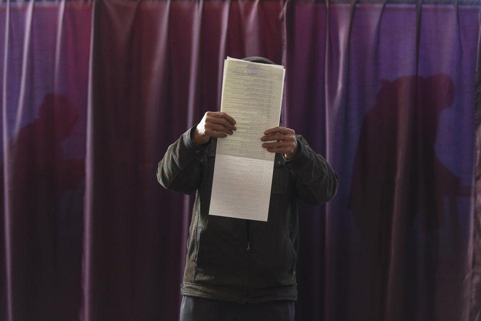 Photo - A man reads a ballot paper before casting his vote for the parliamentary elections at a polling station in Konstantinovka, Donetsk region, eastern Ukraine, Sunday, Oct. 26, 2014. Voters in Ukraine headed to the polls Sunday to elect a new parliament, overhauling a legislature tainted by its association with ousted President Viktor Yanukovych.  (AP Photo/Evgeniy Maloletka)