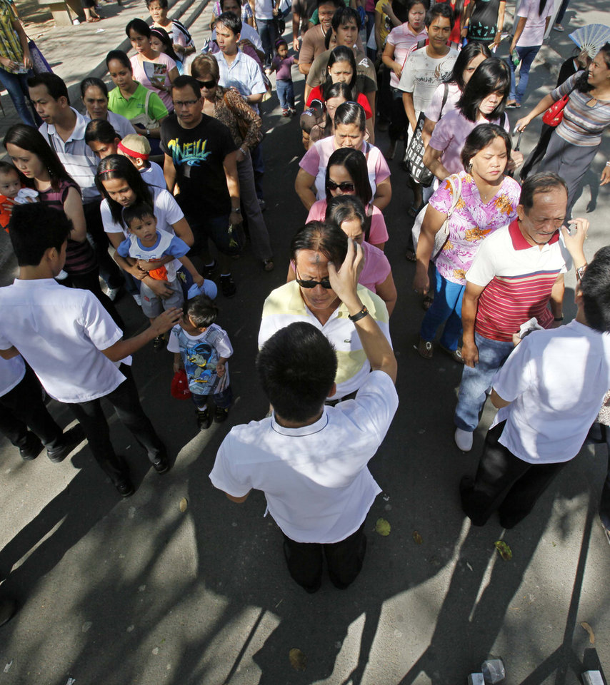 Filipino Catholics line up to have their foreheads applied with ash or soot on Ash Wednesday to usher the 40-day season of Lent Wednesday Feb. 17, 2010 at Redemptorist Cathedral in Manila, Philippines. The Ash Wednesday is observed to remind mankind of being mortals. (AP Photo/Bullit Marquez)
