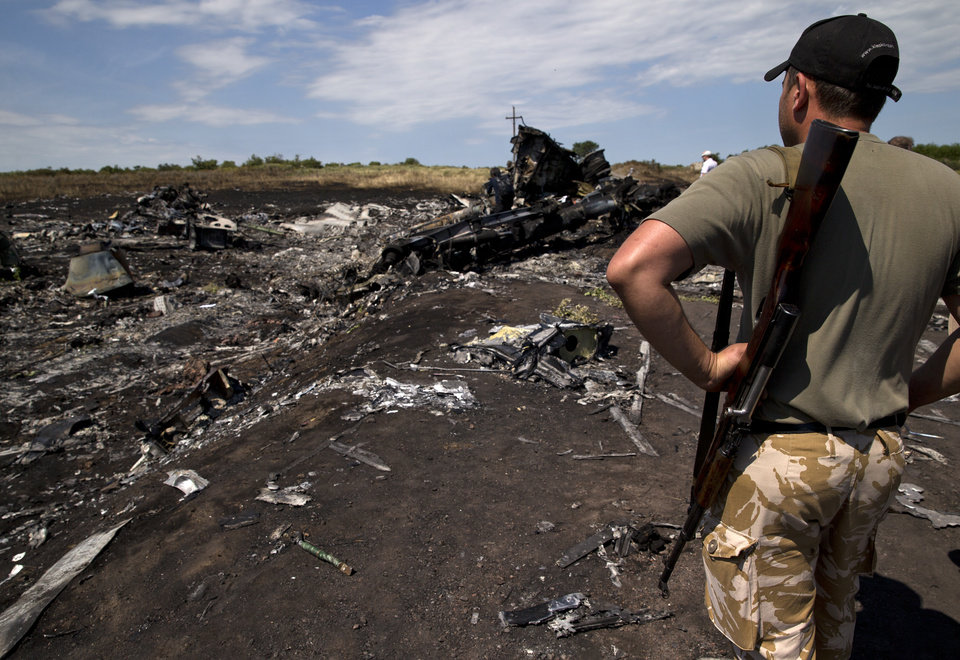 Photo - An armed man looks at charred debris at the crash site of Malaysia Airlines Flight 17 near the village of Hrabove, eastern Ukraine, Sunday, July 20, 2014. Armed rebels forced emergency workers to hand over all 196 bodies recovered from the Malaysia Airlines crash site and had them loaded Sunday onto refrigerated train cars bound for a rebel-held city, Ukrainian officials and monitors said. (AP Photo/Vadim Ghirda)