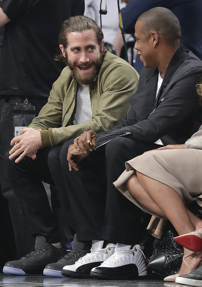 Photo - Actor Jake Gyllenhaal, left, and entertainer Jay-Z talk during a timeout during Game 3 of an Eastern Conference semifinal NBA playoff basketball game between the Miami Heat and the Brooklyn Nets, Saturday, May 10, 2014, in New York. (AP Photo/Julie Jacobson)