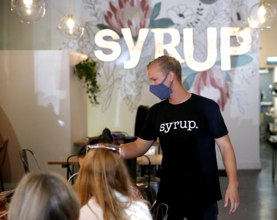 Photo -  Nick Gunzelman helps customers at Syrup in downtown Norman, Okla. Friday, July 24, 2020. [Sarah Phipps/The Oklahoman]