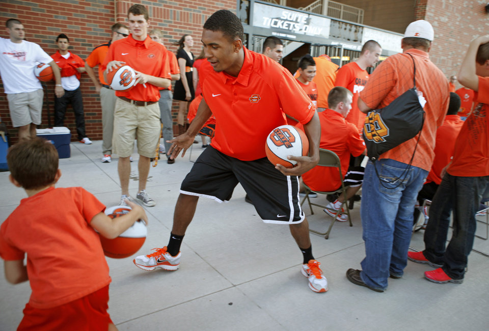 Photo - Heralded OSU freshman basketball player LeBryan Nash plays with fans before the OSU-Arizona football game Thursday night in Stillwater. PHOTO BY BRYAN TERRY, The Oklahoman