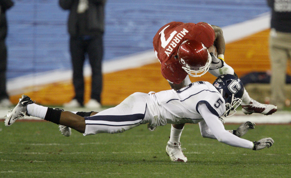 Photo - Oklahoma's Demarco Murray (7) is brought down by Connecticut's Blidi Wreh-Wilson (5) during the Fiesta Bowl college football game between the University of Oklahoma Sooners and the University of Connecticut Huskies in Glendale, Ariz., at the University of Phoenix Stadium on Saturday, Jan. 1, 2011.  Photo by Bryan Terry, The Oklahoman