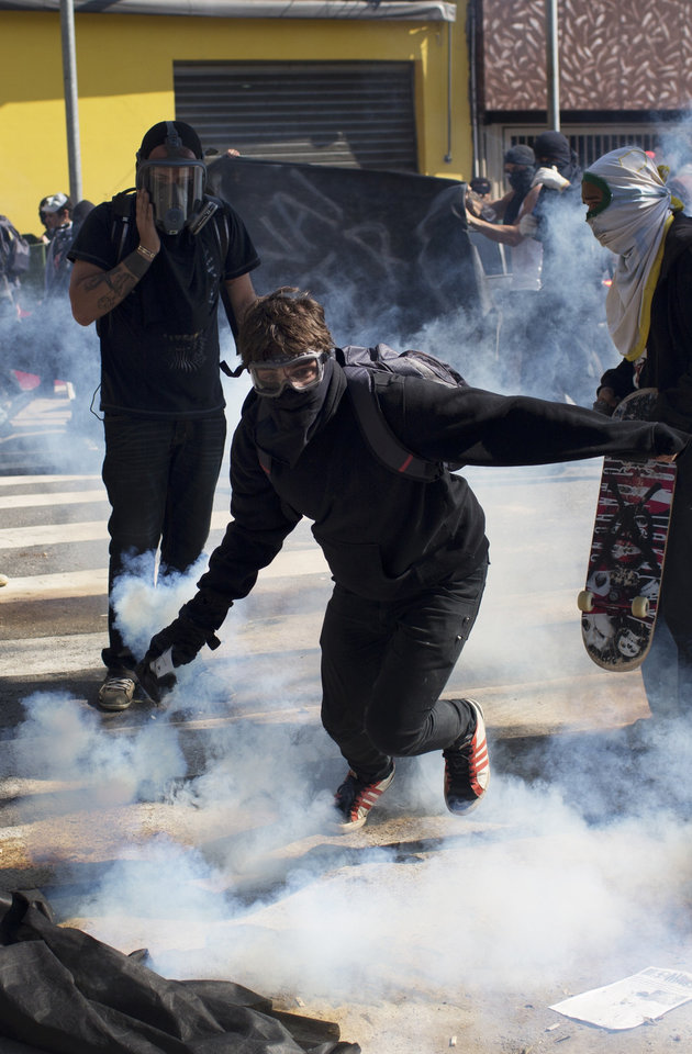 Photo - A masked protester returns a tear gas canister to riot police during a demonstration by people demanding better public services and against the money spent on the World Cup soccer tournament in Sao Paulo, Brazil, Thursday, June 12, 2014. Brazilian police clashed with anti-World Cup protesters trying to block part of the main highway leading to the stadium that hosts the opening match of the tournament. (AP Photo/Rodrigo Abd)