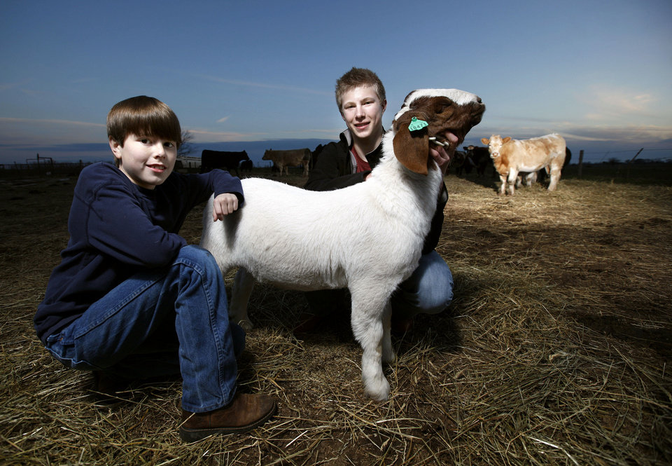 Photo - Carson, right, and Garrett Lough pose with a goat at a barn in Hennessey on Thursday. Photo by Sarah Phipps, The Oklahoman  SARAH PHIPPS