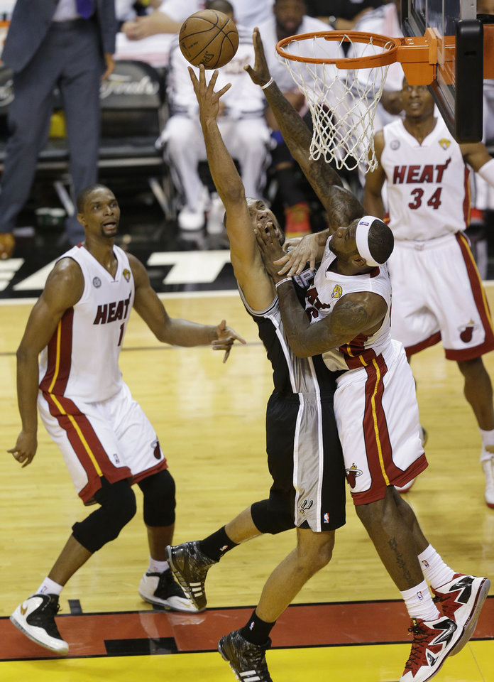 Photo - San Antonio Spurs power forward Tim Duncan (21) and Miami Heat small forward LeBron James (6) collide under the basket during the first half of Game 2 of the NBA Finals basketball game, Sunday, June 9, 2013 in Miami.  (AP Photo/Wilfredo Lee)