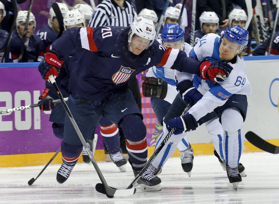 Photo - USA defenseman and Finland forward Mikael Grandlund vie for the puck during the second period of the men's bronze medal ice hockey game at the 2014 Winter Olympics, Saturday, Feb. 22, 2014, in Sochi, Russia. (AP Photo/Mark Humphrey)