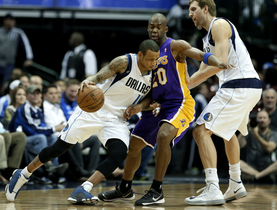 Photo - Dallas Mavericks' Monta Ellis (11) drives through Los Angeles Lakers' Jodie Meeks (20) as Dirk Nowitzki, right, sets the pick in the first half of an NBA basketball game, Tuesday, Jan. 7, 2014, in Dallas. (AP Photo/Tony Gutierrez)