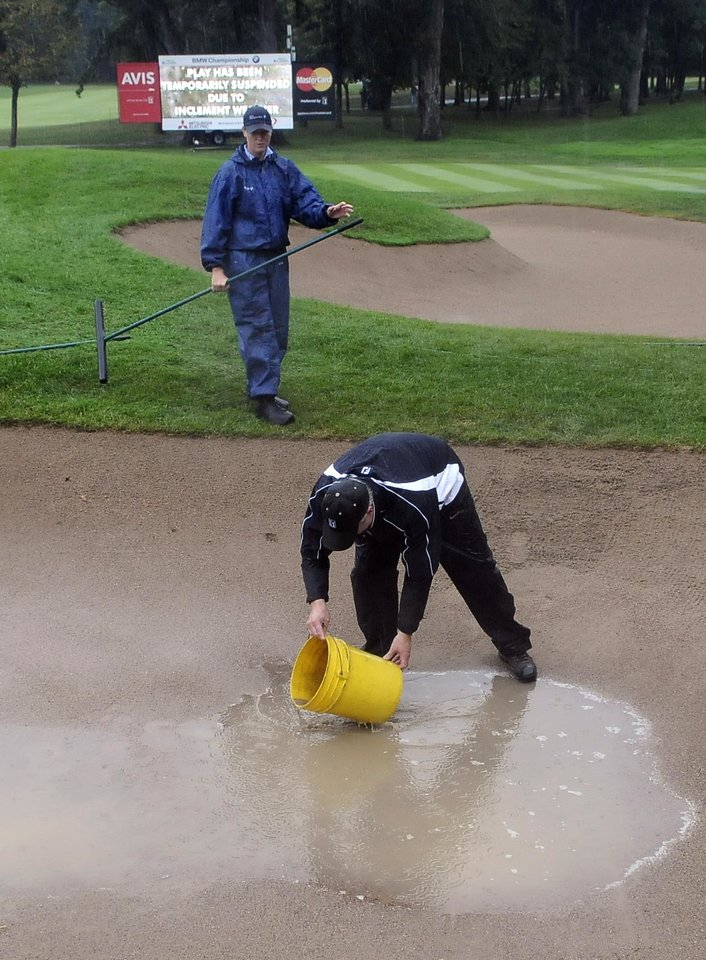 Photo - Volunteers Kurt Galisdorfer, bottom, and Heather Hemming remove water from a sand trap on the second hole during a rain delay in the final round of the BMW Championship golf tournament at Conway Farms Golf Club in Lake Forest, Ill., Sunday, Sept. 15, 2013. (AP Photo/Matt Marton)