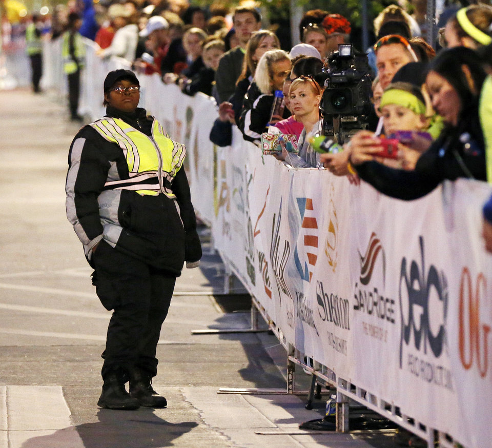 Photo - Spectators wait along Harvey Ave. as a security guard keeps watch before the start of the Oklahoma City Memorial Marathon in Oklahoma City, Sunday, April 28, 2013. Photo by Nate Billings, The Oklahoman