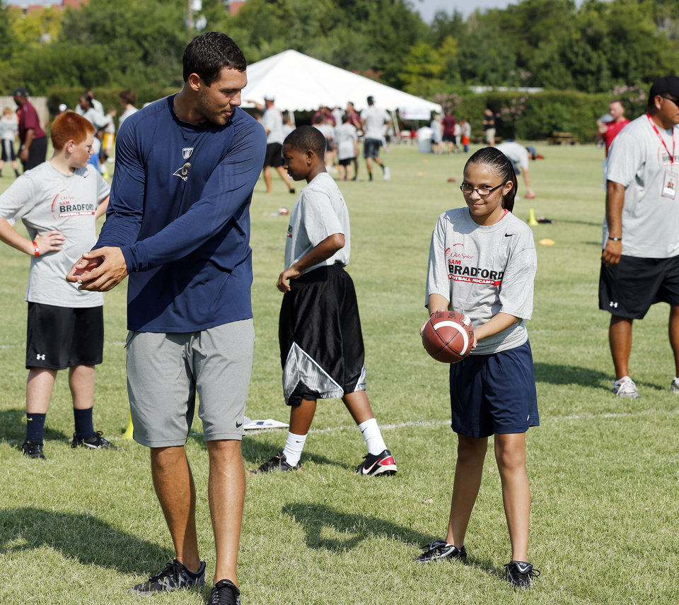 Photo - Sam Bradford works with camper Isabel Tamez, 12, from Oklahoma City during his football camp on the campus of the University of Oklahoma on Tuesday, July 10, 2012, in Norman, Okla. Photo by Steve Sisney, The Oklahoman  STEVE SISNEY