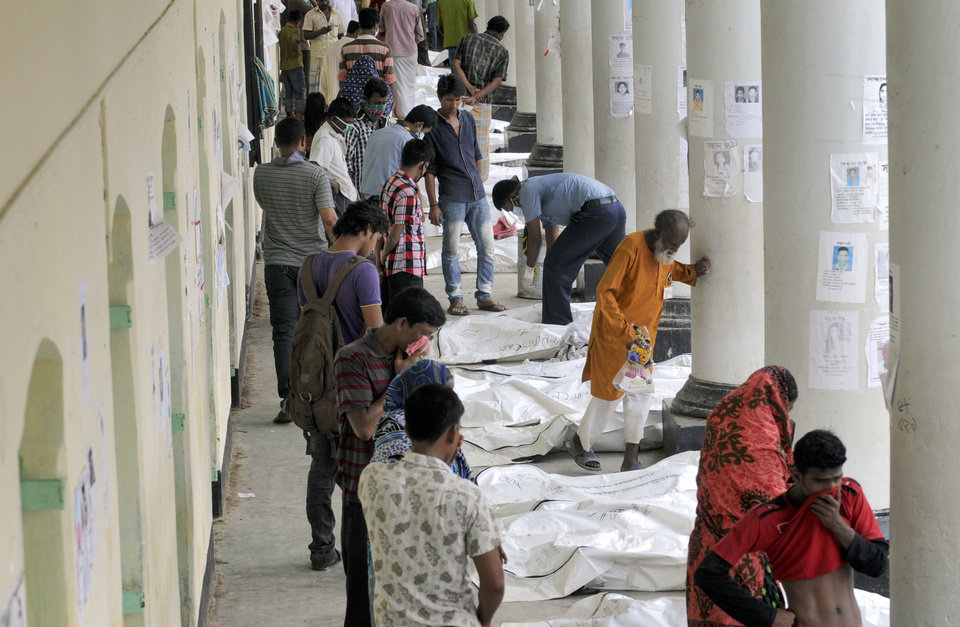 Photo - Bangladeshis look for their missing relatives along a row of dead bodies laid out near the site of a garment factory building that collapsed in Savar near Dhaka, Bangladesh, Wednesday May 8, 2013. Dozens of bodies recovered Wednesday from the building were so decomposed they were being sent to a lab for DNA identification, police said, as the death toll from Bangladesh's worst industrial disaster topped 800. (AP Photo/Ismail Ferdous)