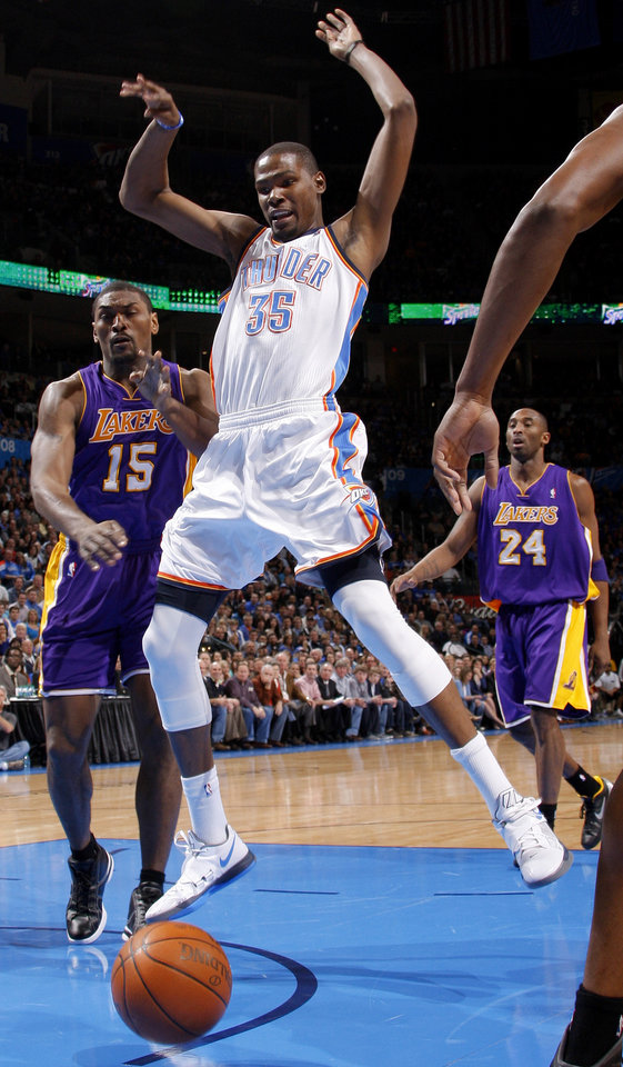 Photo - Kevin Durant (35) loses control of the ball between Metta World Peace (15) and Kobe Bryant (24) during an NBA basketball game between the Oklahoma City Thunder and the Los Angeles Lakers at Chesapeake Energy Arena in Oklahoma City, Thursday, Feb. 23, 2012. Photo by Bryan Terry, The Oklahoman