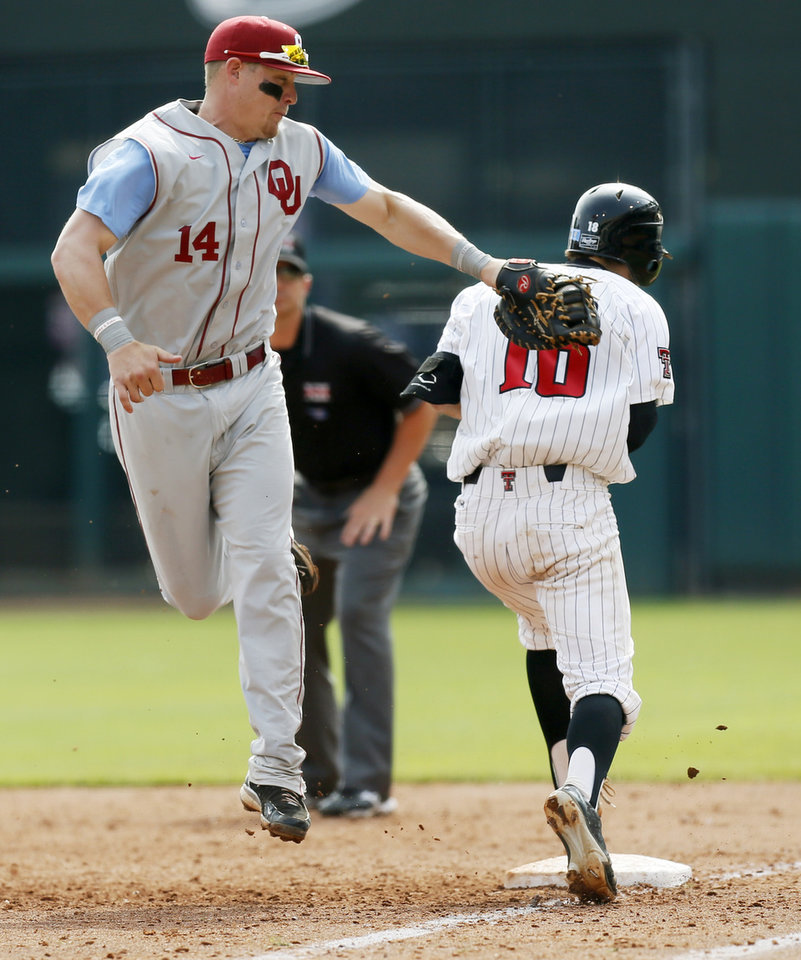 Photo - Texas Tech's Mason Randolph (18) safely runs to 1st base past OU's Matt Oberste (14) in the 5th inning during an NCAA baseball game between Oklahoma and Texas Tech in the Big 12 Baseball Championship tournament at the Chickasaw Bricktown Ballpark in Oklahoma City, Friday, May 24, 2013. OU won 8-0. Photo by Nate Billings, The Oklahoman