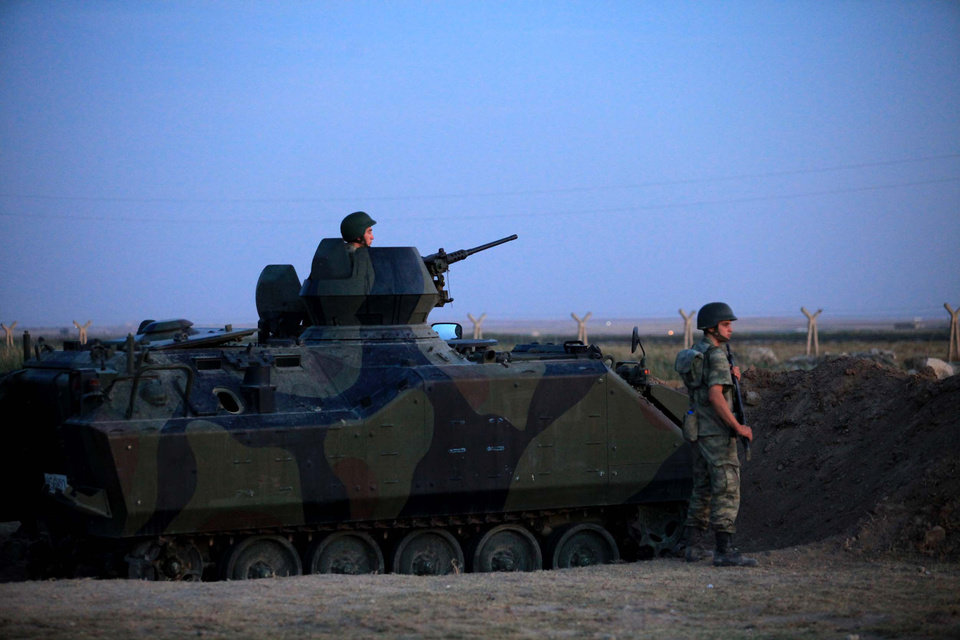 Photo -   Turkish military stand near the Turkey-Syria border in Akcakale, Turkey, early Friday, Oct. 5, 2012. Turkey fired on Syrian targets for a second day Thursday, but said it has no intention of declaring war, despite tensions after deadly shelling from Syria killed five civilians in a Turkish border town. (AP Photo)