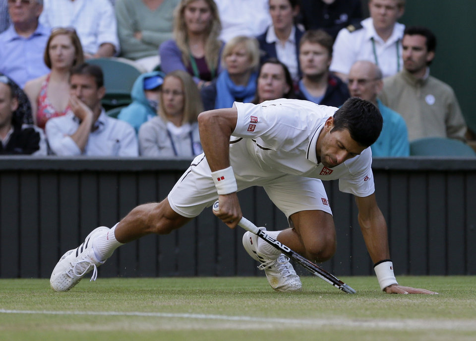 Photo - Novak Djokovic of Serbia slides as he plays Tommy Haas of Germany during a Men's singles match at the All England Lawn Tennis Championships in Wimbledon, London, Monday, July 1, 2013.  (AP Photo/Alastair Grant)