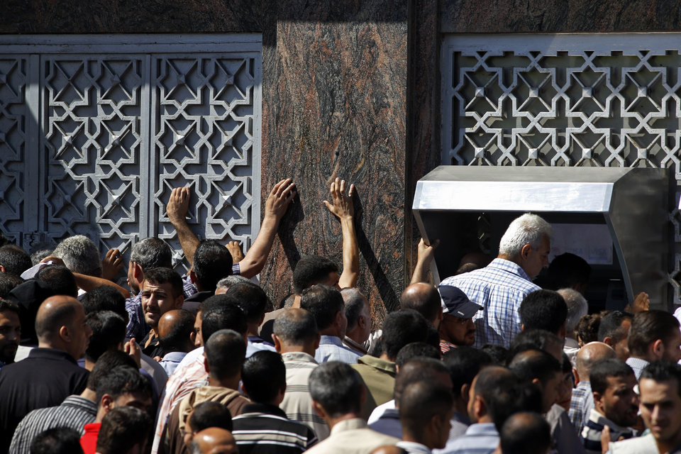 Photo - Palestinians gather to withdraw money from ATM machines in Gaza City, Thursday, July 17, 2014. The Bank of Palestine opened one of its branches in Gaza City's Rimal neighborhood as the cease-fire began, drawing hundreds of people trying to withdraw money. The Israeli military says it has struck 37 targets in Gaza ahead of a five-hour humanitarian cease-fire meant to allow civilians to stock up after 10 days of fighting. Palestinian health officials say that in total, at least 225 Palestinians have been killed. On the Israeli side, one man was killed since July 8. (AP Photo/Lefteris Pitarakis
