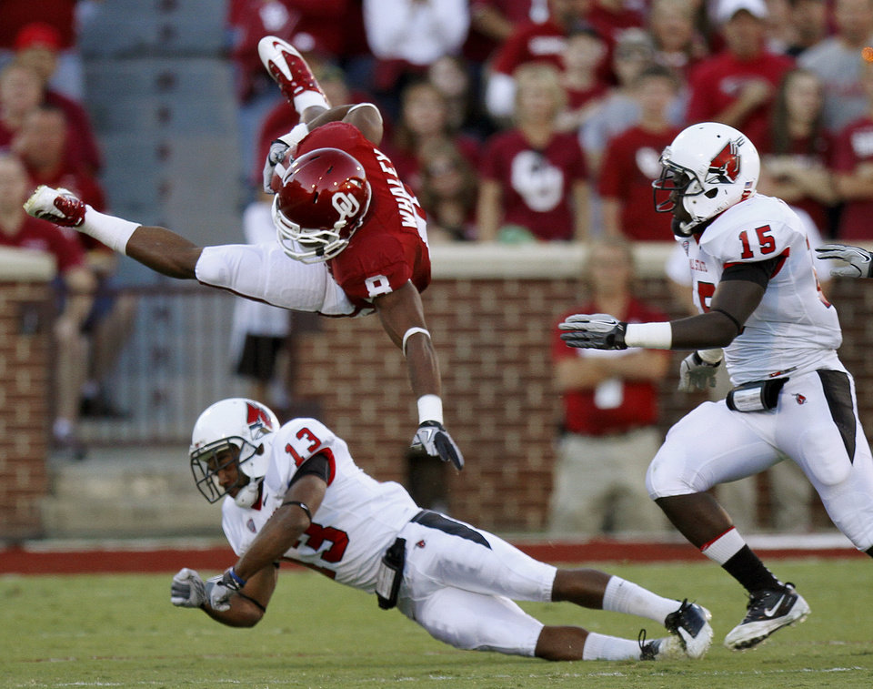Photo - Oklahoma's Dominique Whaley (8) leaps over Ball State's Armand Dehaney (13) as Aaron Morris (15) trails during the college football game between the University of Oklahoma Sooners (OU) and the Ball State Cardinals at Gaylord Family-Memorial Stadium on Saturday, Oct. 01, 2011, in Norman, Okla. Oklahoma won 62-6. Photo by Bryan Terry, The Oklahoman