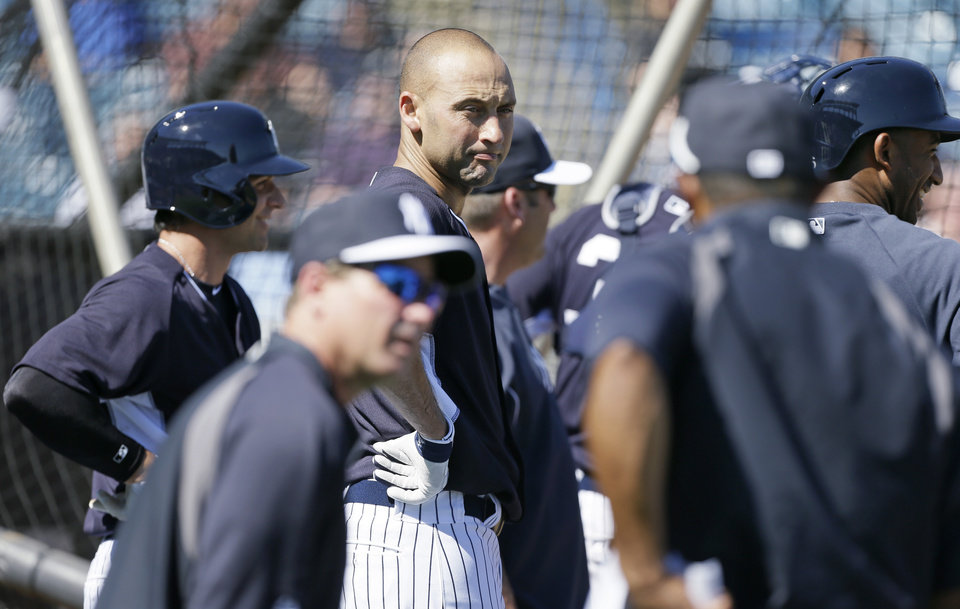 Photo - New York Yankees shortstop Derek Jeter, center, waits to hit in the batting cage during spring training baseball practice Thursday, Feb. 20, 2014, in Tampa, Fla. (AP Photo/Charlie Neibergall)