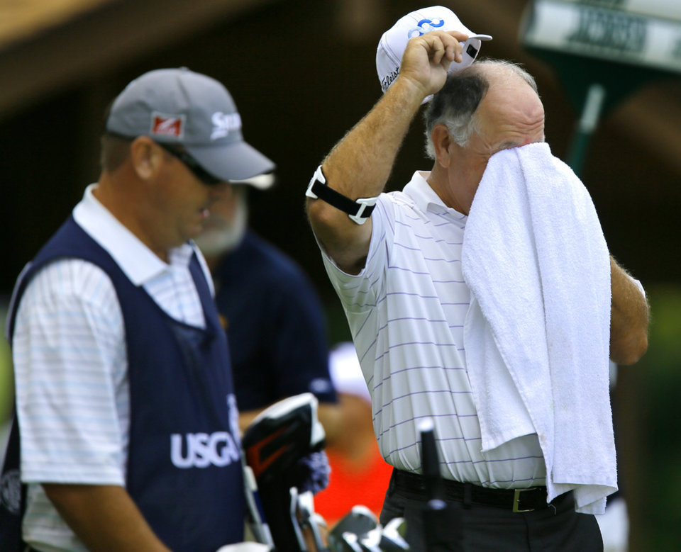 Photo - Mark O'Meara wipes the sweat from his face before taking a tee shot on the eighth hole during the first round of the U.S. Senior Open Championship golf tournament at Oak Tree National in Edmond, Okla. on Thursday, July 10, 2014. Photo by Chris Landsberger, The Oklahoman