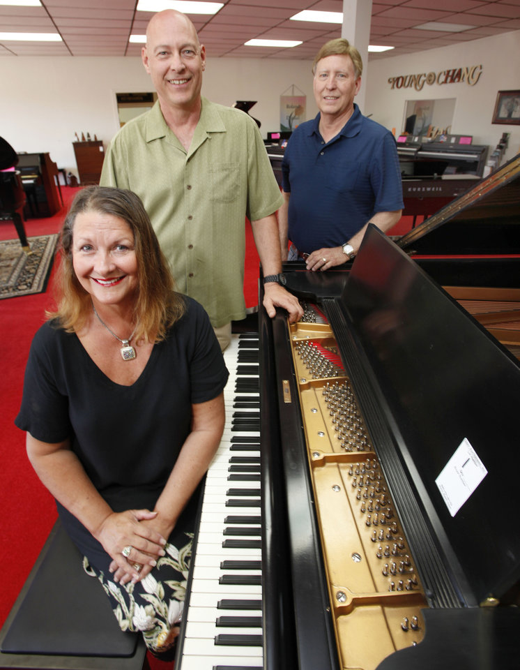 Albert Evans\' children Elaine Evans Walters, Phillip Evans, left, and Steve Evans surround a restored 1911 Baldwin piano at their late father\'s store at 4100 N MacArthur Blvd. Auctioneer Louis Dakil will sell the real estate and liquidate the inventory at auctions on Saturday at his warehouse, 200 NW 114. Steve Gooch - The Oklahoman