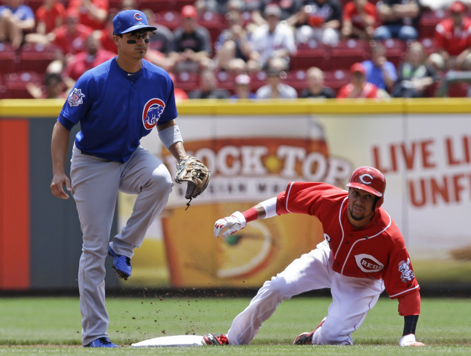 Photo - Cincinnati Reds' Billy Hamilton, right, steals second base as Chicago Cubs second baseman Darwin Barney waits for the throw in the first inning of a baseball game, Tuesday, July 8, 2014, in Cincinnati. (AP Photo/Al Behrman)