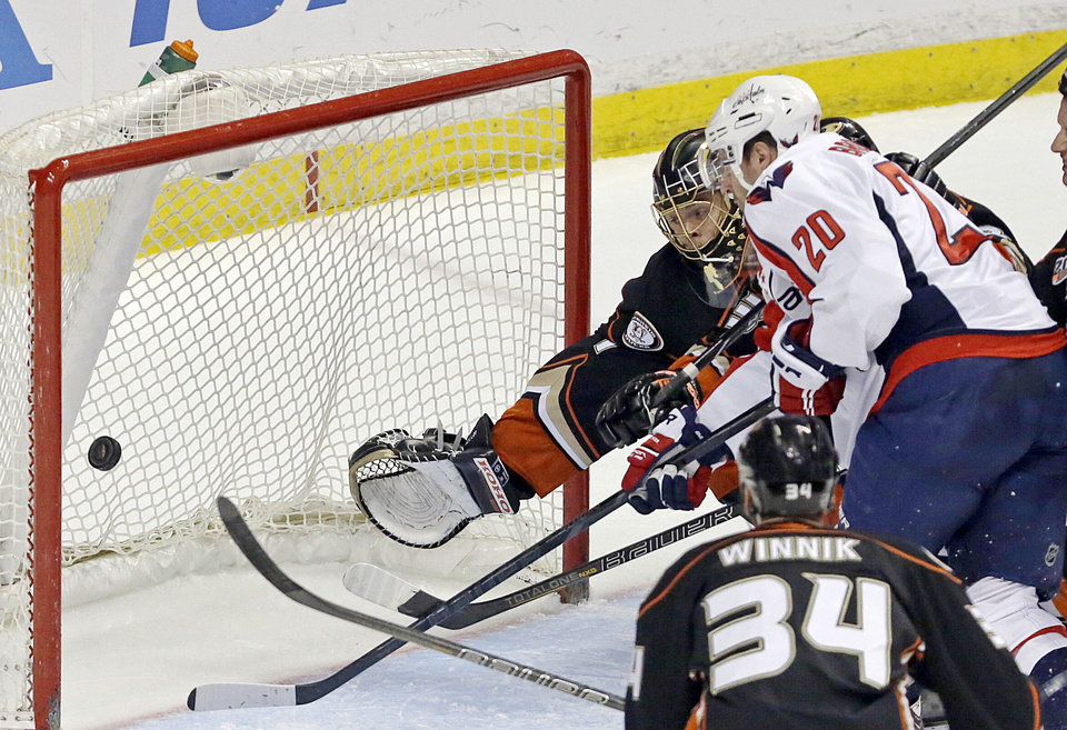 Photo - Washington Capitals right winger Troy Brouwer (20) scores on a wrist shot past Anaheim Ducks goalie Jonas Hiller (1), of Switzerland, and center Daniel Winnik (34) in the first period of an NHL hockey game Tuesday, March 18, 2014. (AP Photo/Reed Saxon)