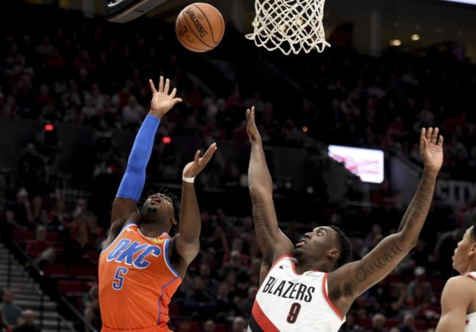 Photo -  Oklahoma City Thunder guard Luguentz Dort, left, shoots the ball over Portland Trail Blazers forward Nassir Little during Sunday night's game in Portland. [AP Photo/Steve Dykes]