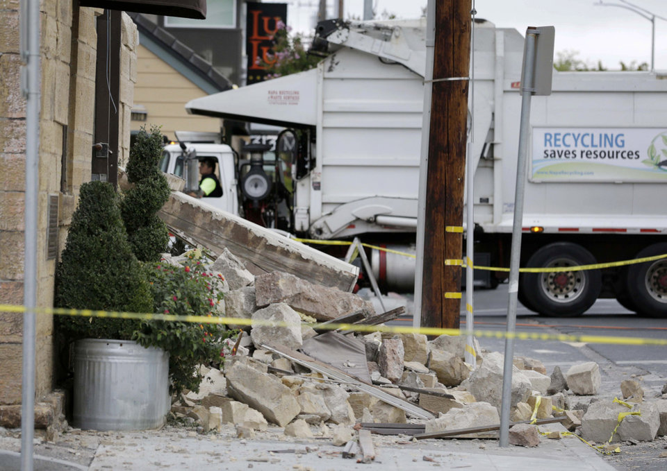 Photo - A garbage truck moves past rubble in front of the earthquake damaged Vintners Collective multi-winery tasting room Monday, Aug. 25, 2014, in Napa, Calif. The building dates from the late 1800s. The San Francisco Bay Area's strongest earthquake in 25 years struck the heart of California's wine country early Sunday, igniting gas-fed fires, damaging some of the region's famed wineries and historic buildings, and sending dozens of people to hospitals. (AP Photo/Eric Risberg)