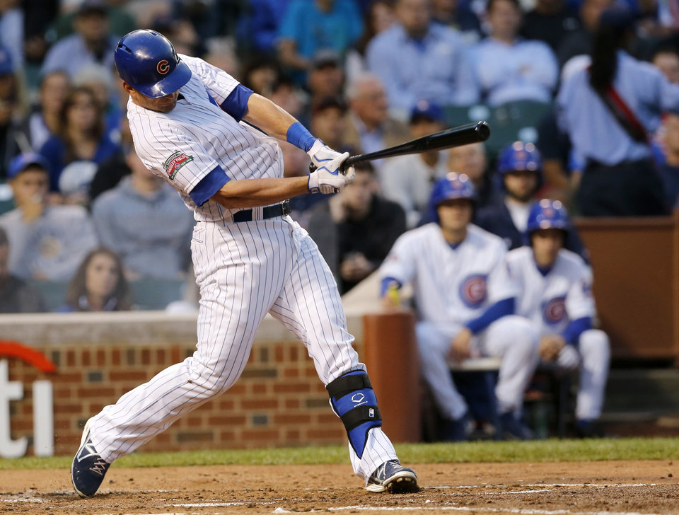 Photo - Chicago Cubs' Justin Ruggiano hits an RBI single off Milwaukee Brewers starting pitcher Wily Peralta, scoring Arismendy Alcantara, during the second inning of a baseball game Tuesday, Aug. 12, 2014, in Chicago. (AP Photo/Charles Rex Arbogast)