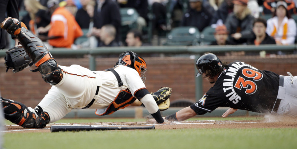 Photo - Miami Marlins' Jarrod Saltalamacchia (39) scores past the tag attempt by San Francisco Giants catcher Hector Sanchez on a single from Adeiny Hechavarria during the second inning of a baseball game on Saturday, May 17, 2014, in San Francisco. (AP Photo/Marcio Jose Sanchez)