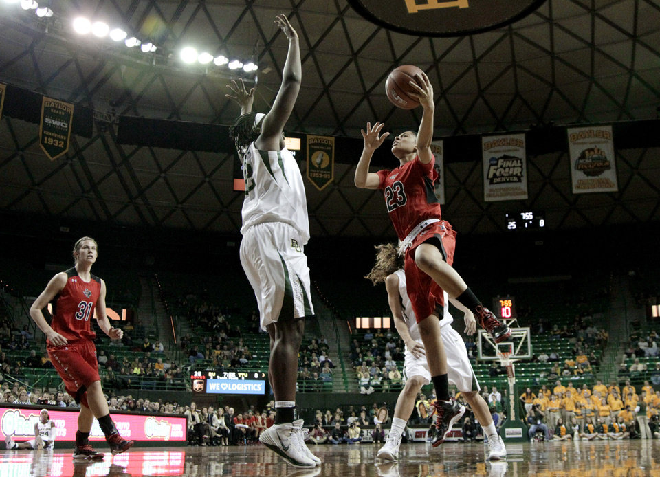 Photo - Baylor center Sune Agbuke (22) moves into position to block a shot by Texas Tech's Jasmine Caston (23) as Haley Schneider (31) watches in the first half of an NCAA college basketball game, Wednesday, Jan. 29, 2014, in Waco, Texas. (AP Photo/Tony Gutierrez)