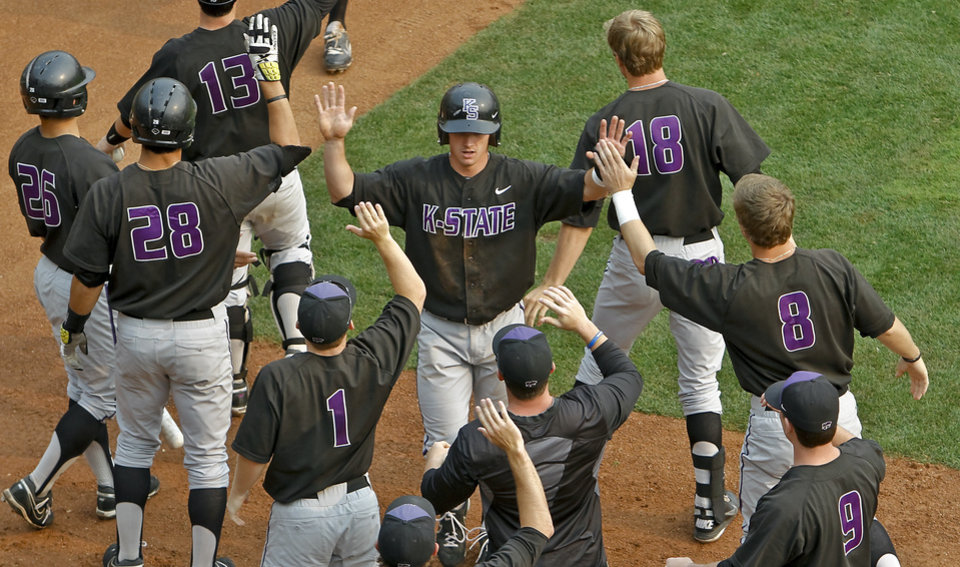Kansas State's Tanner Witt, center,  celebrates with teammates after scoring a run during the Big 12 baseball tournament game between Oklahoma State University  and Kansas State University at the Chickasaw Bricktown Ballparkon Thursday, May 24, 2012, in Oklahoma City, Oklahoma. Photo by Chris Landsberger, The Oklahoman