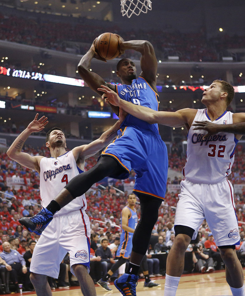Photo - Oklahoma City's Serge Ibaka (9) gets a rebound as Los Angeles' J.J. Redick (4) and Blake Griffin (32) defend during Game 6 of the Western Conference semifinals in the NBA playoffs between the Oklahoma City Thunder and the Los Angeles Clippers at the Staples Center in Los Angeles, Thursday, May 15, 2014. Photo by Nate Billings, The Oklahoman
