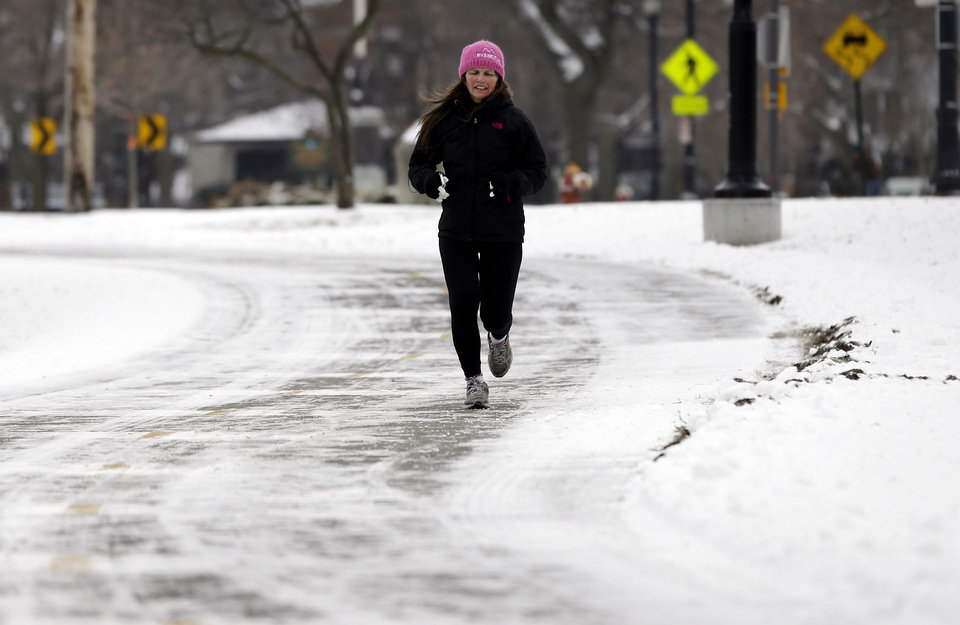 Photo - A jogger runs along a snow-covered street in Evanston, Ill., Friday, Jan. 25, 2013. The 1.1 inches that settled on Windy City streets and sidewalks marked the latest first seasonal snowfall of at least an inch in the Midwest metropolis since at least 1884, when records were first kept, National Weather Service forecaster Matt Friedlein said. The previous record was set on Jan. 17, 1899. Friday also broke Chicago's longest streak of consecutive days without an inch of snow. The city went 335 days, or about 11 months, without at least an inch, Friedlein said. (AP Photo/Nam Y. Huh)
