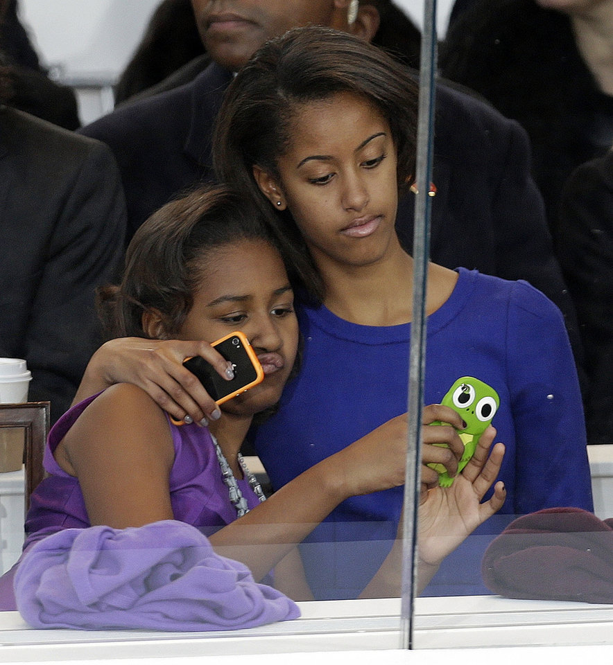 Photo - Malia Obama, right, and Sasha Obama look on from the presidential box during the Inaugural parade, Monday, Jan. 21, 2013, in Washington. Thousands  marched during the 57th Presidential Inauguration parade after the ceremonial swearing-in of President Barack Obama. (AP Photo/Gerald Herbert)