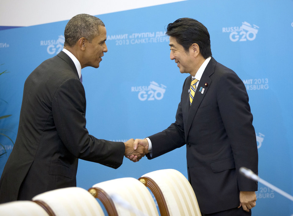 Photo - US President Barack Obama, left, and Japan's Prime Minister Shinzo Abe, right, shake hands before the start of their bilateral meeting at the G20 Summit, Thursday, Sept. 5, 2013 in St. Petersburg, Russia. (AP Photo/Pablo Martinez Monsivais)