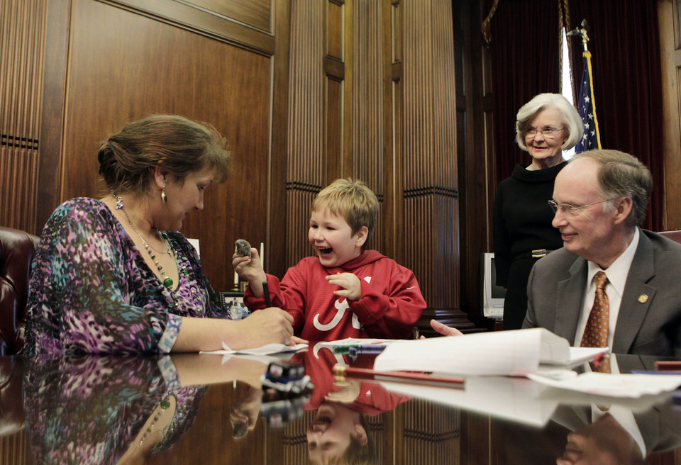 Photo - In this photo provided by the Governor's office, from right to left, Alabama Gov. Robert Bentley and First Lady Dianne Bentley watch as Ethan Gilman shows his mother, Jennifer Kirkland, a toy mouse Bentley gave him to play with on a visit to the Governor's Office in Montgomery, Ala. on Wednesday, Feb. 13, 2012. Ethan was held hostage in an underground bunker in a near week-long standoff in Midland City, Ala. (AP Photo/Alabama Governor's Office, Jamie Martin)