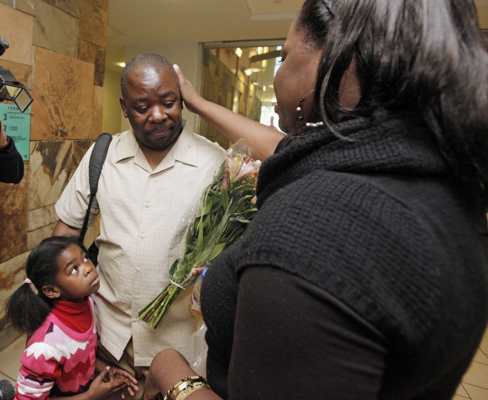 Photo - RETURN / HOMECOMING: Humphreys Munai,  middle, is greeted by his wife, Judith McCarty-Munai, right, and daughter, Imani Munai, 5, after arriving at Will Rogers World Airport in Oklahoma City, Thursday, January 14, 2010. Humphreys Munai was returning from Haiti where he was working for World Neighbors when the recent earthquake devastated the country. Photo by Nate Billings, The Oklahoman ORG XMIT: KOD