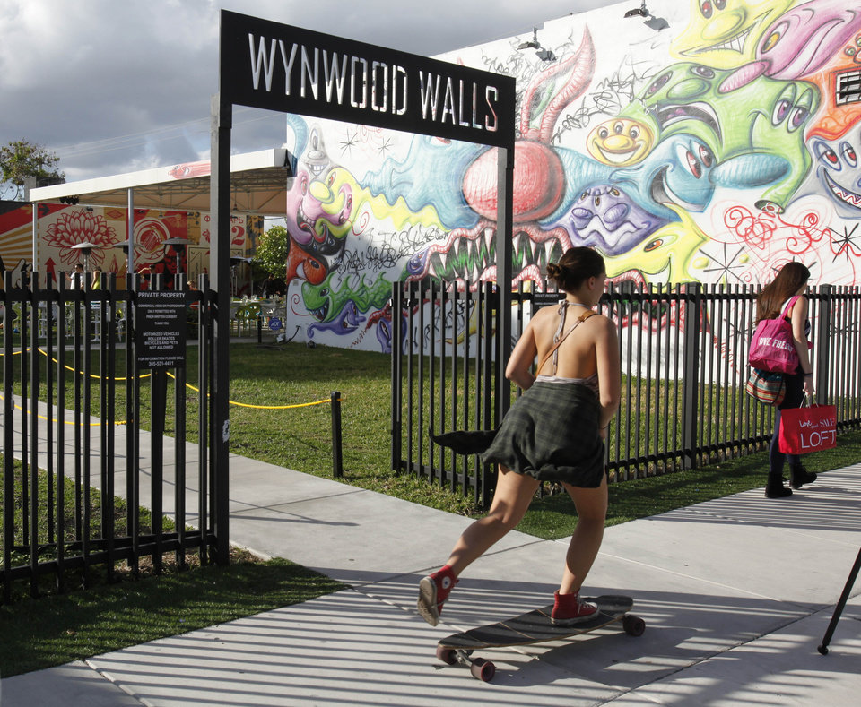 A skateboarder and pedestrian pass the entrance to Wynwood Walls, Monday, Dec. 3, 2012 in Miami. Art Basel Miami Beach and about two dozen other independent art fairs open Thursday. Tens of thousands of people are expected through Sunday at the fairs throughout Miami and South Beach. Street artists, including Shepard Fairey, have painted colorful new works onto the exteriors of the warehouses and building of the Wynwood district. (AP Photo/Wilfredo Lee)