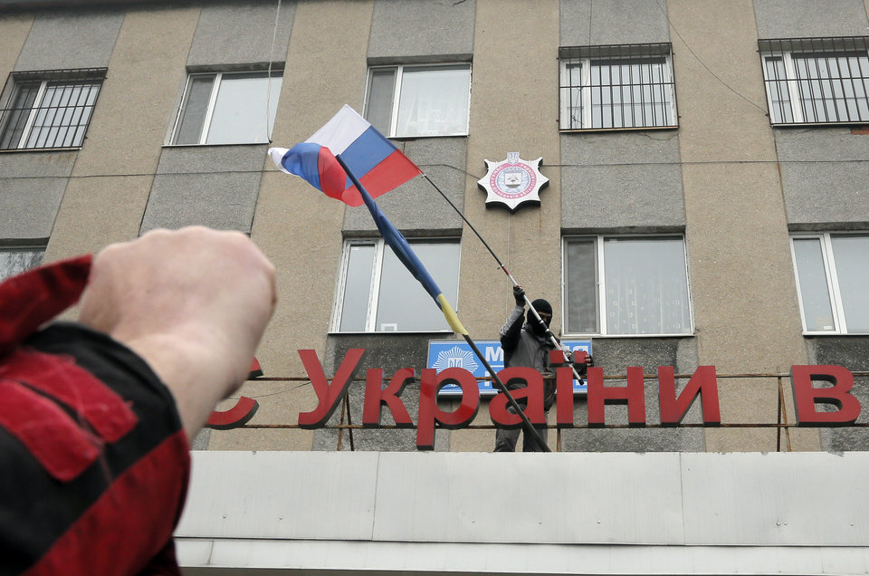 Photo - A pro-Russian man places a Russian flag over a police station during its mass storming in the eastern Ukrainian town of Horlivka on Monday, April 14, 2014.  The text reads: Ukrainian police station in Horlivka