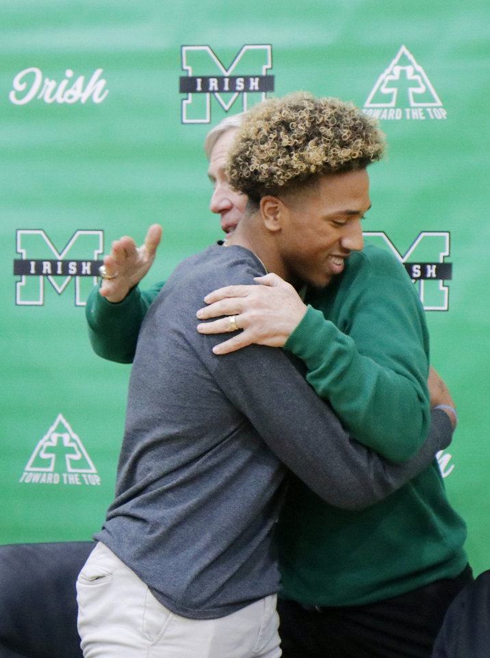 Photo - Principal David Morton congratulates Dominic Richardson, McGuinness, who commited to TCU during National Signing Day for high school football players, Wednesday, December 18, 2019. [Photo by Doug Hoke/The Oklahoman]