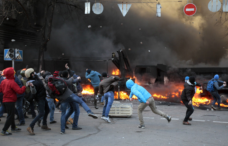 Photo - Anti-government protesters clash with riot police outside Ukraine's parliament in Kiev, Ukraine, Tuesday, Feb. 18, 2014. Ukraine's festering political crisis took a deadly turn Tuesday, as thousands of anti-government protesters clashed with police outside Ukraine's parliament. Three protesters were killed in the melee, the opposition reported, and emergency workers found another person dead after a fire at the ruling party's office in Kiev. Law enforcement agencies gave the demonstrators a deadline of 6 p.m. (1600 GMT) to stop the confrontations and vowed to restore order. (AP Photo/Sergei Chuzavkov)
