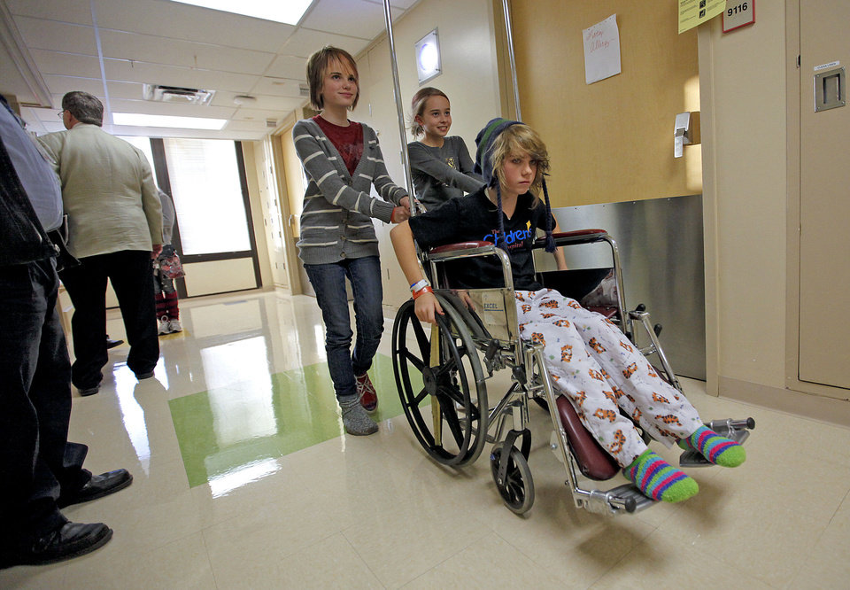 Photo - Savanna Gable, left, and Liz Smith wheel Ambri Tygard back to her room after the three spoke to the media about their injuries and experience of being trapped under an elevator at Classen School of Advance Studies during a press conference at the OU Medical Center Children's Hospital on Thursday, Nov. 17, 2011. in Oklahoma City.  Photo by Chris Landsberger, The Oklahoman  CHRIS LANDSBERGER