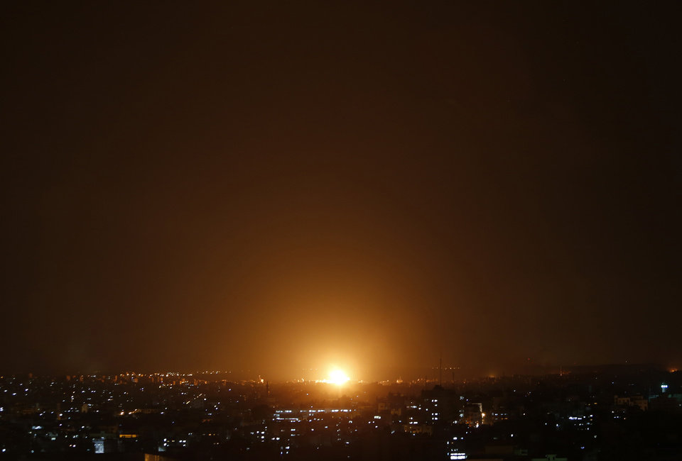 Photo - An explosion by an Israeli strike is seen in Gaza City, northern Gaza Strip, late Saturday, July 19, 2014. Gaza Health Ministry spokesman Ashraf al-Kidra said the new round of strikes raised the death toll from the 12-day offensive to more than 330 Palestinians, many of them civilians and nearly a fourth of them under the age of 18.(AP Photo/Lefteris Pitarakis)
