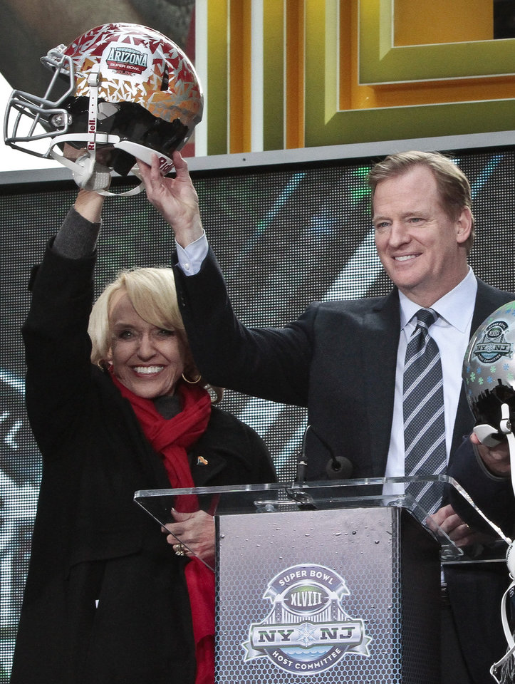 Photo - Arizona Gov. Jan Brewer, left, raise a souvenir football helmet with NFL Commissioner Roger Goodell, during a ceremony to pass official hosting duties of next year's Super Bowl to Arizona, Saturday Feb. 1, 2014 in New York.   (AP Photo/Bebeto Matthews)